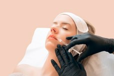 Woman giving botox injections. Young woman gets beauty facial injections in the cosmetology salon. Face aging injection. Aesthetic Medicine, Cosmetology