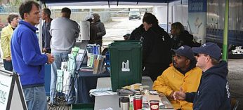 Dhinesh Sivananthan and Gavin Tyler, seated, answer questions and offer advice to people ridding their homes of junk at Ward 43's Environment Day at 891 Morningside Ave. last Saturday.