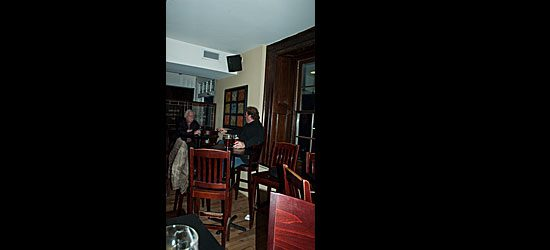 These regular Stone Cottage patrons enjoy their beers at the corner table by the door.