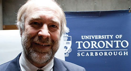 Tom Nowers, Dean of Student Affairs, U of T Scarborough, stands in front of a UTSC sign.
