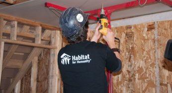 Habitat volunteer drills in drywall screw