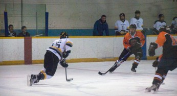 RH King Academy assistant captain, Landon McGhee #15, skates through two Bendale defenders.
