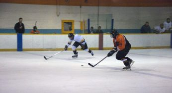Tiger's Burtt #8, skates into the offensive zone, trying to beat a Lion's defender.