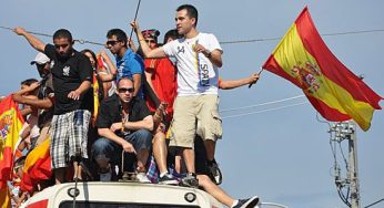 A group of men cheer and wave a flag on top of a 506 streetcar