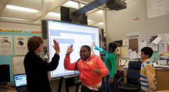 Fara Clermont gives her teacher Joan Debrie a high five after playing a game of hang man using the Smart Board. When the students touch the correct letter a soccer ball scores a goal on the screen.
