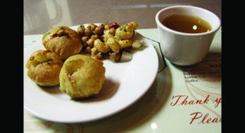 Pani puri — hollow balls of crispy dough, filled with potatoes, chickpeas, onions and spicy tamarind water.