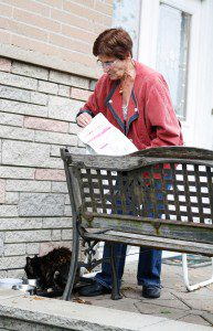 Scarborough resident Dorothy Mathieson feeds stray cats in front of her house. Her house is a gathering place for a colony of about 25 feral cats mostly born in the street.