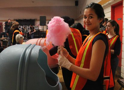A student volunteer makes some cotton candy for a festival-goer. There were approximately 60 high school volunteers that participated during Winterfest.