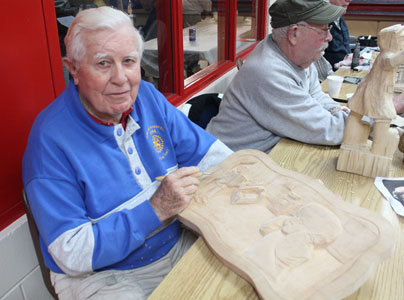 Relief wood carver Jim Foster works on a piece during Winterfest. He says he has been making woodcarvings for 80 years.