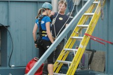 A participant gets harnessed up on the roof in preparation of the rappel.