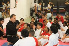 Master Lou Milonas answers his young students' questions during a Team UMAC's Kids Martial Arts program lesson.