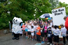 Kids posing for a group with panda mascot before Cub Run begins.