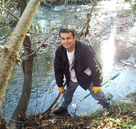 Patrick Couture picks up garbage at Highland Creek during Centennial College's community cleanup Oct. 20.