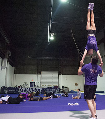 "Travis Stirrat demonstrating a skill. He has 14 years of experience. Dynasty Cheer Academy to him is a, ""combination between sports acrobatics, power tumbling, gymnastics, trampoline,"" he said."
