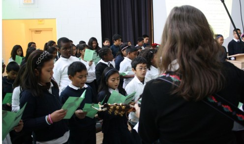 Between speeches and prayers, the students sang hymns accompanied by their choir teacher Kitty, from St. Barnabas Parish.
