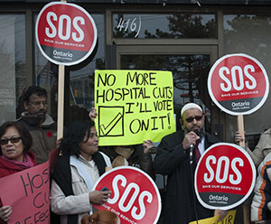 Mushtaq Sayed, holding the mic, rallies the group of demonstrators during a stop of the Nov. 9 Day of Action. The rolling rally made stops at five local MPP offices to protest against hospital funding cuts.