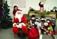 Habitat for Humanity Toronto events officer Sally Ding poses with Santa Claus at the charity's 11th annual Gingerbread Build on Dec. 8.