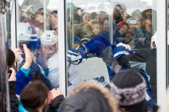 Leafs grapple against the boards.