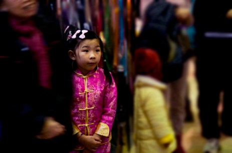 A young girl, dressed in a variation of the traditional Chinese qipao, watches the festivities at the mall.