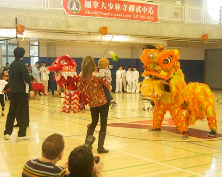 Beth Morgan stands with the orange dragon while the audience is intrigued.