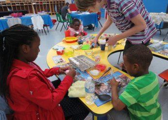 Volunteer helps the children paint eggs.