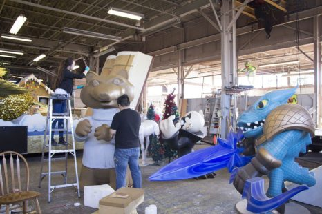 Workers painting float characters.