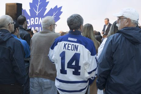 A fan wearing a Dave Keon jersey awaits the revealing of the statues