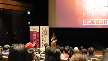 Louanne Chan, Toronto Reel Asian International Festival executive director, addresses audience in Innis College theatre room.