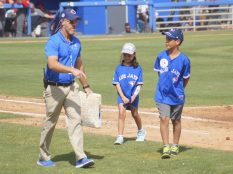 Two fans walk away with a Blue Jays employee after replacing the first base in between innings. (Jonathan Cheng photo)