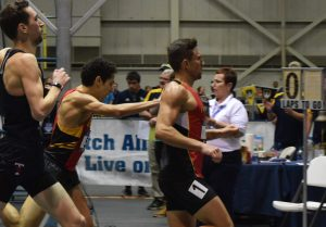 Three runners cross the finish line of a close race.