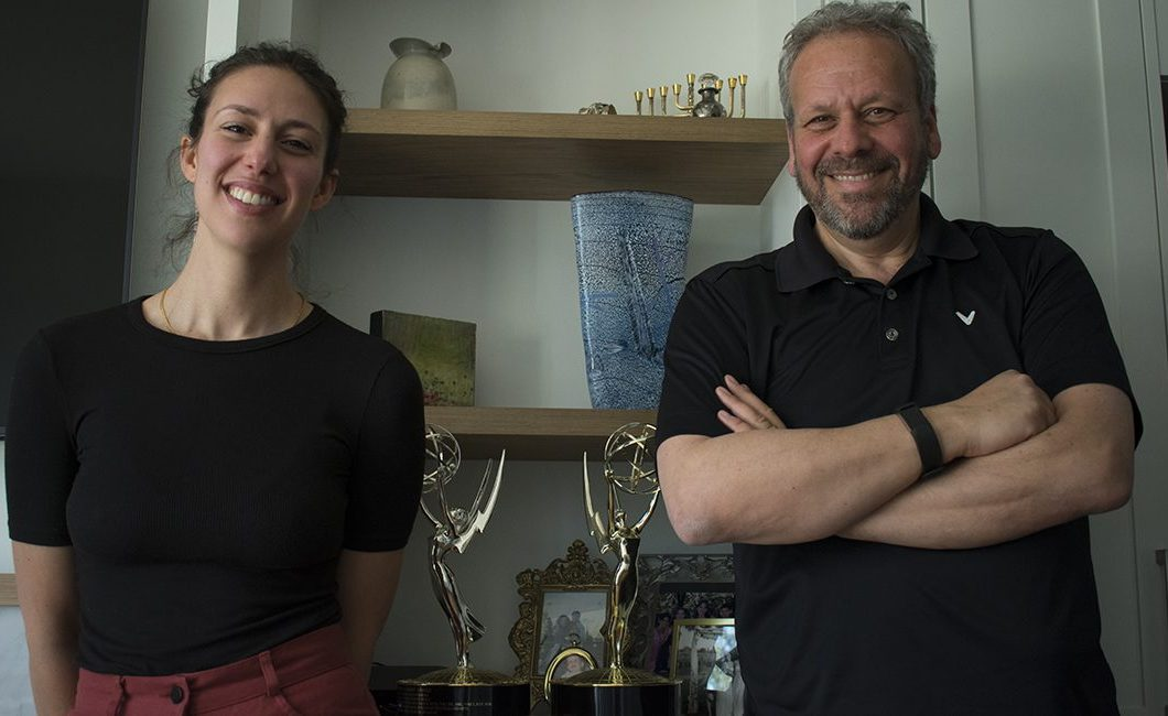 Ali Weinstein and Larry Weinstein standing next to trophies Larry won for previous films.