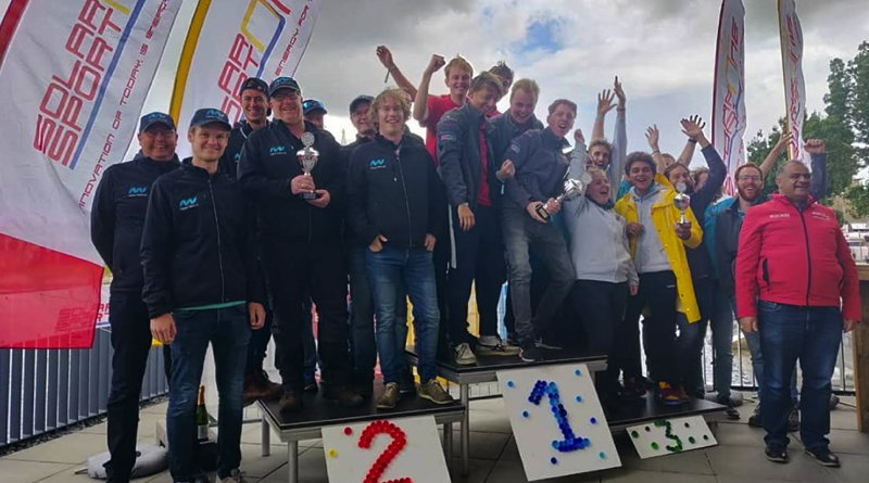 a group of university students, winners of solar boat race celebrate on the podium