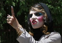 An Afghan woman with make up, argues with a pedestrian, unseen, who told her to leave while waiting for a vehicle in Kabul, Afghanistan on Thursday, June 9, 2011.