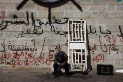 An anti-Gaddafi protester prays near revolutionary graffiti before a rally during Friday prayers in Benghazi March 11, 2011.