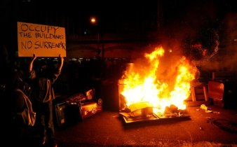 An Occupy Oakland protester raises a sign near a burning trash heap on Thursday, Nov. 3, 2011, in Oakland, Calif.
