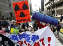 Anti-nuclear protesters shout slogans during a march in front of Tokyo Electric Power Co.'s (TEPCO) headquarters in Tokyo April 10, 2011.