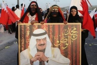Bahraini government supporters hold a portrait of the Gulf kingdom's Prime Minister Khalifa bin Salman al-Khalifa during a rally in Manama on February 22.
