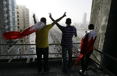 Bahraini youths, with national flags draped around their necks, flash the V-sign for victory as thousands of supporters of Bahrain's Shiite-led opposition march towards Pearl Square in Manama.