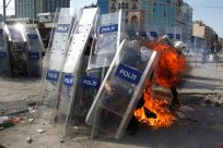 A petrol bomb explodes in front of riot policemen during clashes in Taksim Square in Istanbul, Turkey, Tuesday, June 11, 2013. AP Kostas Tsironis