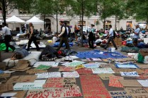 Morning commuters walk past Occupy Wall Street campaign protesters sleeping in Zuccotti Park in New York