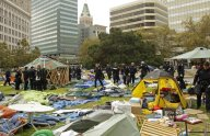 Oakland police officers walk amid possessions left behind by Occupy Oakland protestors across from City Hall Tuesday, Oct. 25, 2011, in Oakland, Calif.