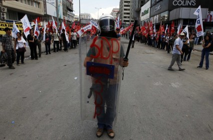An anti-government protester is pictured with a helmet, shield and baton seized from riot police, in Ankara