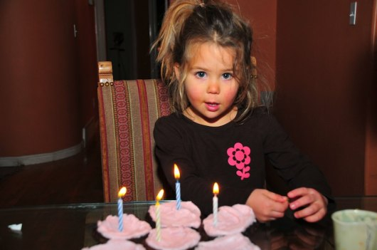 4 cupcakes with candles.