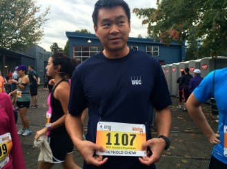 """Reynold Chow shows his bib number before the start of the race. He's here with his team of eight co-workers, all from BGC Engineering. Chow works as a hydroecologist at BGC, an international consulting firm, where he studies water in ground for mining companies for environmental impact assessments. Originally from Toronto, Chow has seen a difference in work-life balance during his two years at BGC. """"A lot of people enjoy the outdoors here,"""" Chow says. """"I think people try to live a more balanced life in Vancouver."""" It's the third year Chow's co-workers have run the Turkey Trot as a team, and he hoped to beat his time of 46 minutes from last year. Chow would finish just shy of his 2013 time, in 98th place."""