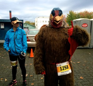 A runner in a turkey costume flashes a thumbs up before the race begins. Outfits ranged from the Lululemon-clad (the company was founded in Vancouver) to turkey costumes. Here, runners participated in a brief warmup led by the event's emcee.