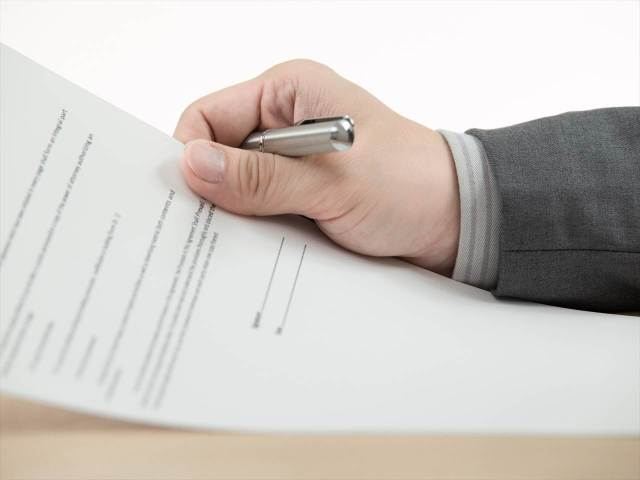 Business man signing finance contract on table
