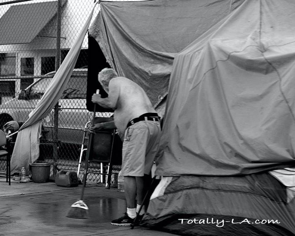 Homeless man sweeping the sidewalk around his tent