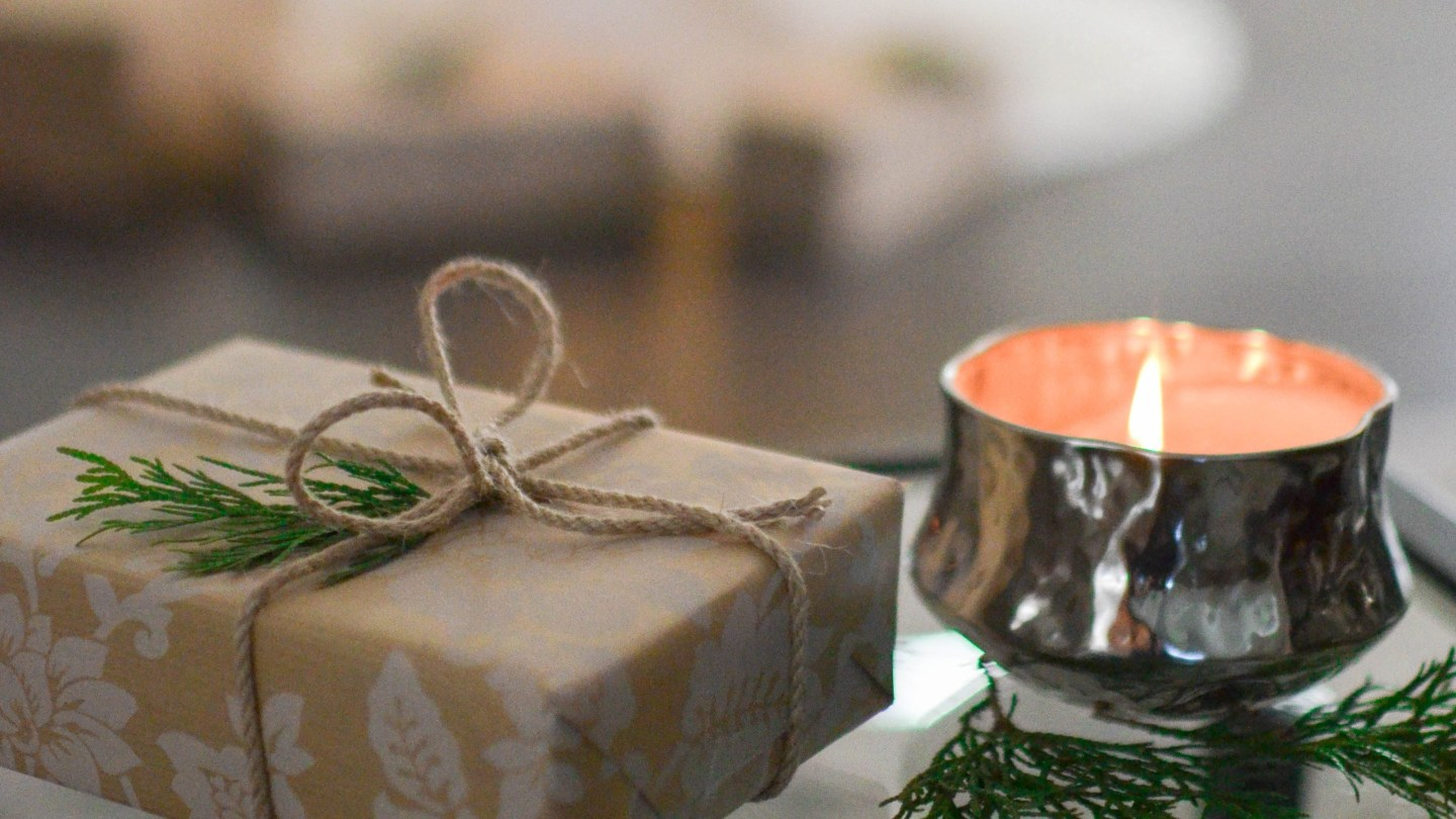 a holiday wrapped package next to a candle