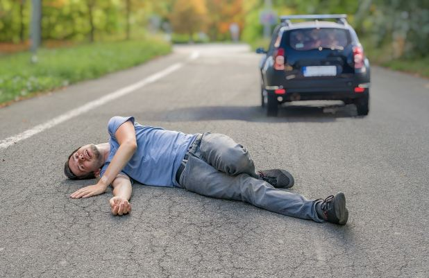 Injured man on road in front of a car.