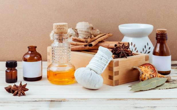 Bottle of essential oil for ayurveda massage with cinnamon stick star anise bay leaves ginger root and herbal compress ball with selective focus on shabby wooden background